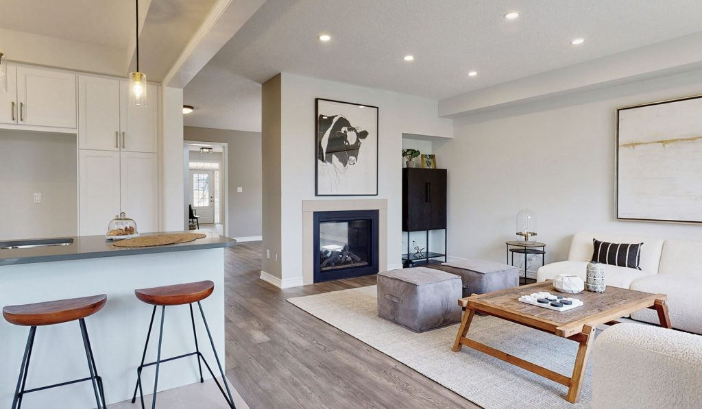 Picture Homes Model Home - Family Living Room With Couch, Fire Place, and Ottomans