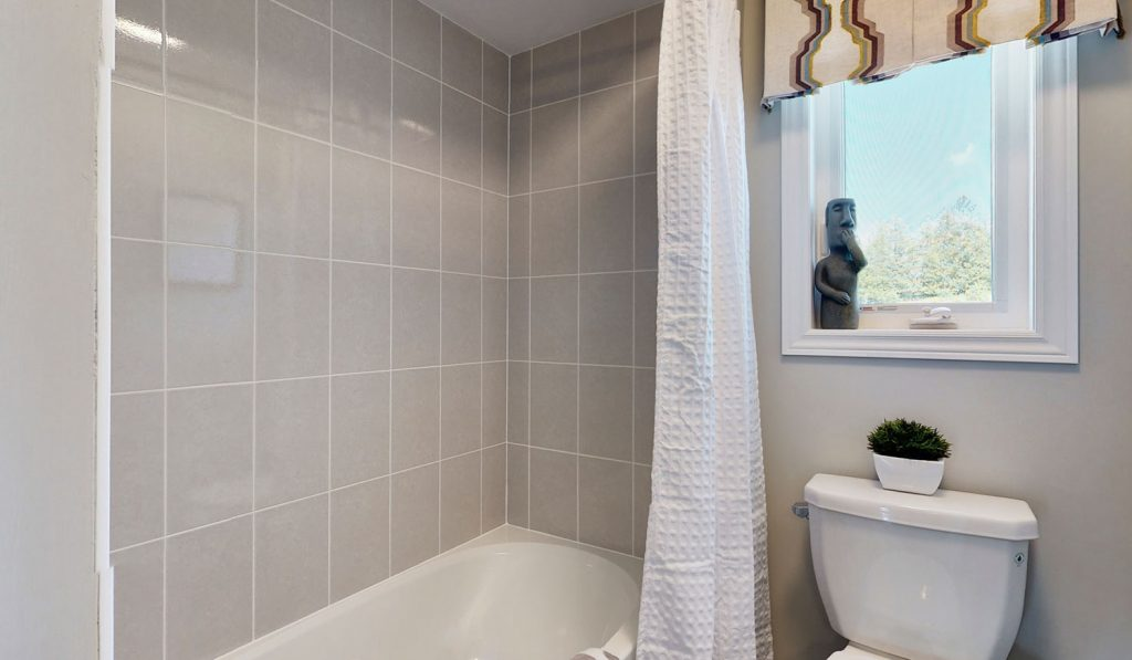 Picture Homes Model Home - Bathtub With Curtain and Toilet in Front of Window in Upstairs Washroom