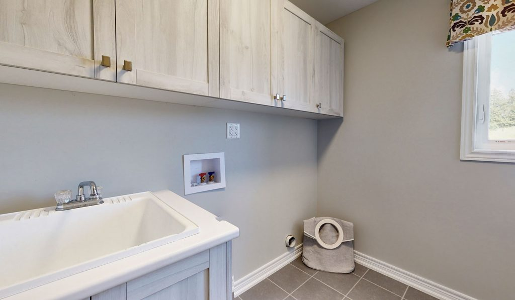 Picture Homes Model Home - Laundry Room with Sink and Storage Shelves
