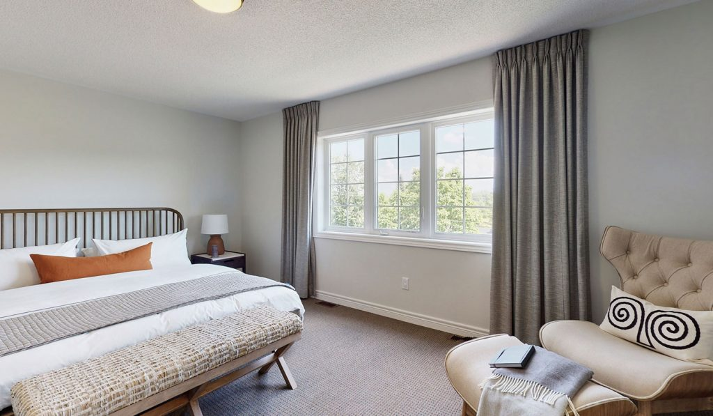Picture Homes Model Home - Bedroom with Large King Bed and Comfortable Chair Beside Window