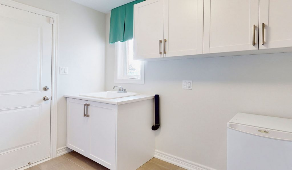 Picture Homes The Hampton Model Home - Laundry Room Sink with Cabinets and Windows