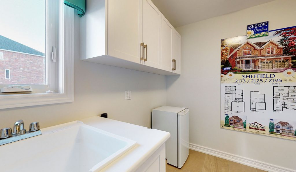 Picture Homes The Hampton Model Home - Laundry Room with White Cabinets