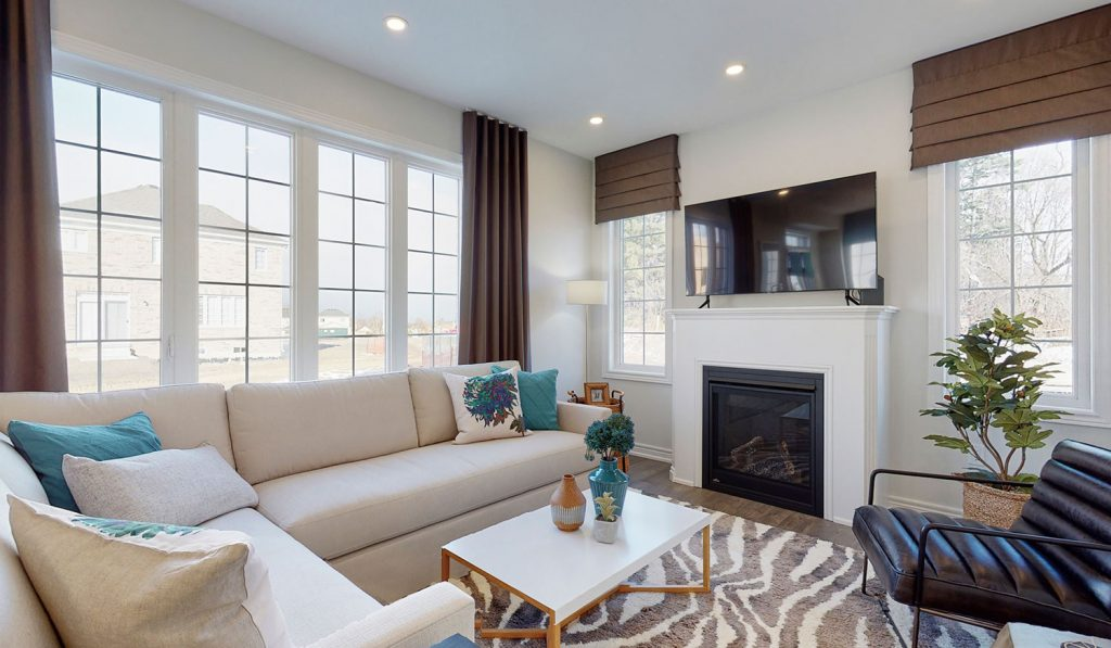 Picture Homes The Hampton Model Home - Family Room Couch, TV, and Fireplace with Large Windows